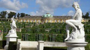Zdjęcie. Rzeźby na postumentach w ogrodzie s tylu francuskim. W tle pałac.