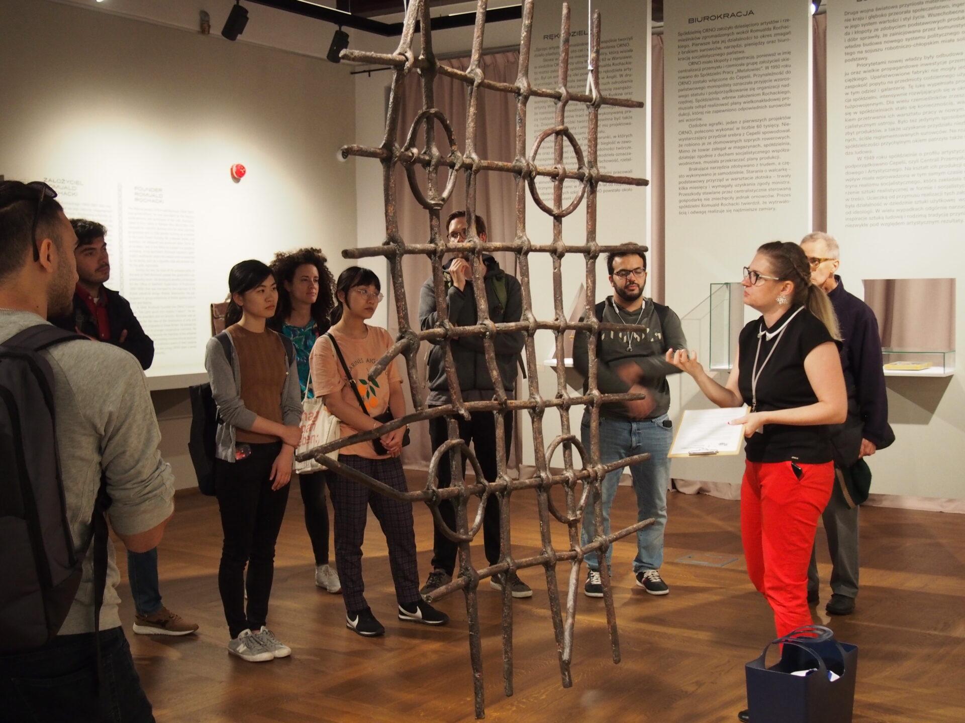Zdjęcie. Ludzie wsali muzealnej słuchają oprowadzającej.