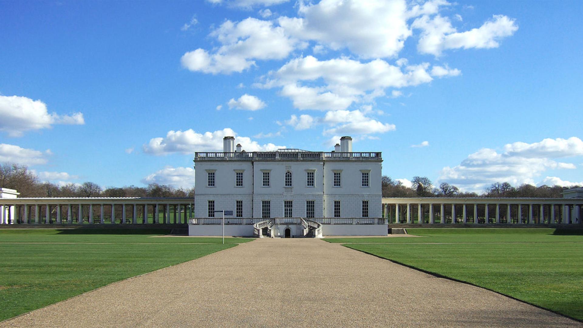London Queens House w głębi kadru, do którego prowadzi aleja, o lewej i prawej trawniki, błękitne niebo